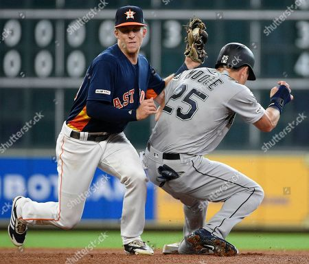 Houston Astros shortstop Myles Straw, left, tags out Seattle Mariners' Dylan Moore during a steal-attempt during the fifth inning of a baseball game, in Houston