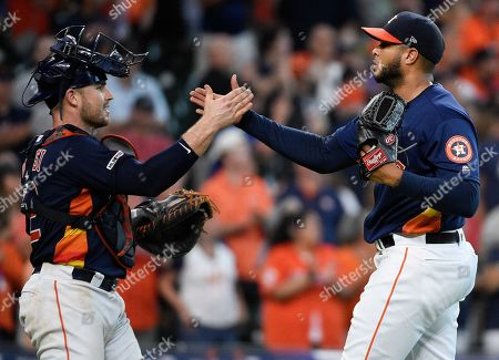 Houston Astros starting pitcher Josh James, right, clasps hands with catcher Max Stassi after the team's win over the Seattle Mariners in a baseball game, in Houston
