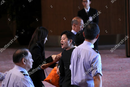 Lawmaker Helena Wong (C) is escorted out of the venue after shouting for Chief Executive Carrie Lam to step down during her speech after the flag raising ceremony to mark the 22nd anniversary of Hong Kong's handover from Britain to China inside the Hong Kong Convention and Exhibition Centre in Hong Kong, China, 01 July 2019. Anti-extradition bill protesters vowed to disrupt a flag-raising ceremony on 01 July 2019. On 01 July, Hong Kong marks the 1997 transfer of sovereignty of Hong Kong from Britain to China.