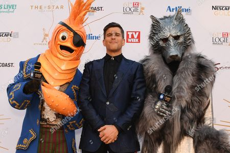 Osher Gunsberg (centre) and characters from the 'The Masked Singer' arrive at the 2019 Logie Awards at The Star Casino on the Gold Coast, Australia, 30 June 2019. ( )