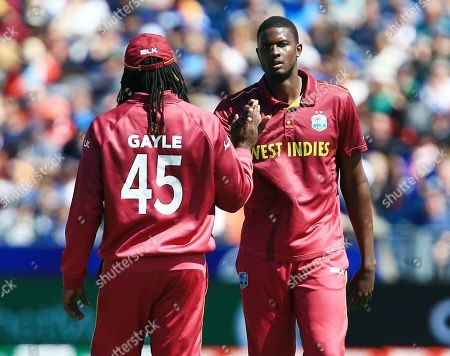 Jason Holder of West Indies celebrates taking the wicket of Dimuth Karunaratne of Sri Lanka with Chris Gayle
