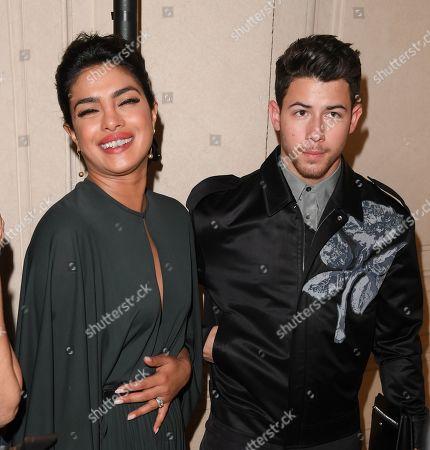 Stock Photo of Priyanka Chopra (holding her tummy) and Nick Jonas in the front row