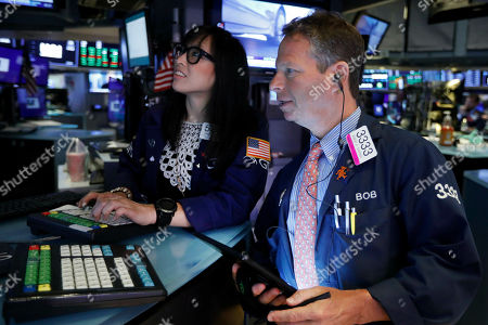 Erica Fredrickson, Robert Charmak. Specialist Erica Fredricks and trader Robert Charmak work on on the floor of the New York Stock Exchange, . Stocks are rallying early Monday after the U.S. and China agreed to resume trade talks