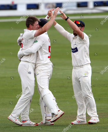 Dan Douthwaite of Glamorgan celebrates with team mates Tom Cullen and David Lloyd after he bowled Callum Ferguson.