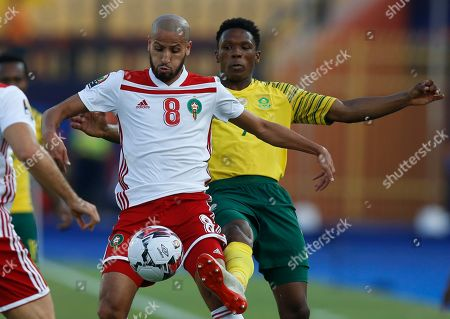 South Africa's Lebo Mothiba, right, and Morocco's Karim El Ahmadi Aroussi fight for the ball during the African Cup of Nations group D soccer match between South Africa and Morocco in Al Salam Stadium in Cairo, Egypt