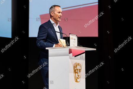 Stock Photo of David Gardner, Vice President for Games at BAFTA, announces the winner of the Mentor award