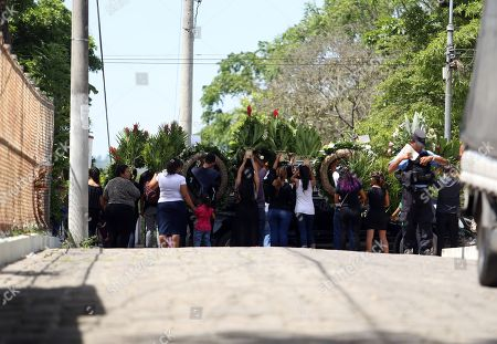 Stock Photo of Attendees try to cover the car carrying the coffins of Oscar Martinez and his daughter Valeria during their funeral, in San Salvador, El Salvador, 01 July 2019. The bodies of Salvadorans Oscar Martinez and his daughter Valeria, who drowned past 23 June at the Rio Bravo while attempting to reach US territory, were buried in San Salvador in a private ceremony.
