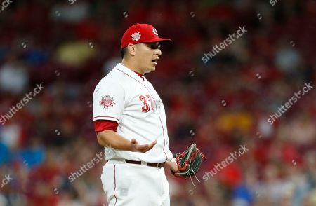 Cincinnati Reds relief pitcher David Hernandez (37) reacts to walking in a run against the Milwaukee Brewers during the seventh inning of a baseball game, in Cincinnati