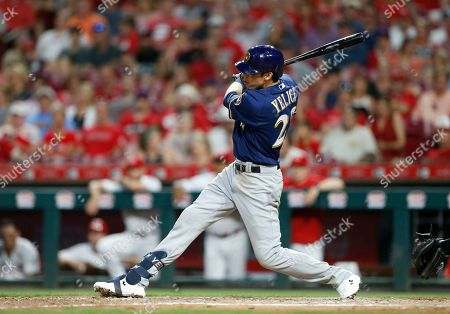 Milwaukee Brewers' Christian Yelich (22) follows through on an RBI single off Cincinnati Reds relief pitcher David Hernandez during the seventh inning of a baseball game, in Cincinnati