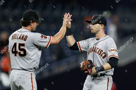 San Francisco Giants right fielder Austin Slater, right, celebrates with starting pitcher Derek Holland (45) after defeating the San Diego Padres 13-2 in a baseball game, in San Diego