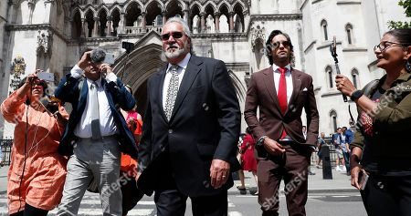 Indian business man Vijay Mallya speaks to the media as he leaves the High Court for a lunch break where he is appealing against extradition to India to face fraud charges at the Royal Courts of Justice in London, . Mallya, whose business empire once included Kingfisher beer, left India two and a half years ago after defaulting on debts of more than a billion dollars linked to a failing venture, Kingfisher Airlines