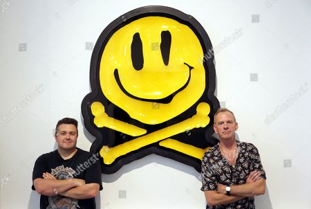 Norman Cook, aka Fat Boy Slim, right, poses with British artist RYCA and his piece titled Bonio 2019 original, at the Underdogs Gallery in Lisbon, . Smile High Club, an exhibition of art works that incorporate the smiley face and curated by Cook was on show at the gallery