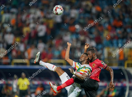 Stock Picture of Masunguna Alex Afonso of Angola and Kalifa Coulibaly of Mali challenging for the ball during the African Cup of Nations match between Angola and Mali at the Ismailia Stadium in Ismailia, Egypt