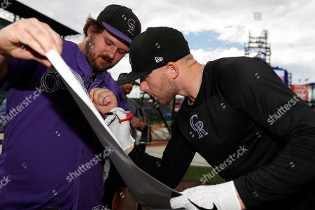 Cameron morris, trevor story, r m. Colorado Rockies shortstop Trevor Story, right, autographs a portrait drawn by Cameron Morris of Loveland, Colo., before a baseball game against the Houston Astros, in Denver