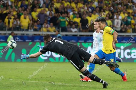 Brazil's Roberto Firmino scores his side's 2nd goal against Argentina's goalkeeper Franco Armani during a Copa America semifinal soccer match at the Mineirao stadium in Belo Horizonte, Brazil