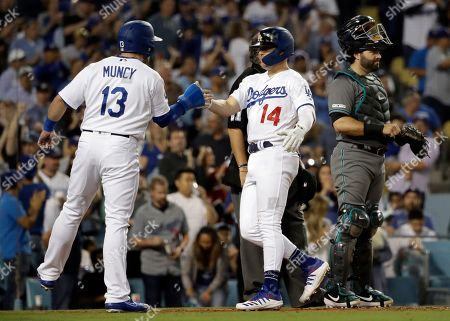 Enrique Hernandez, Max Muncy. Los Angeles Dodgers' Enrique Hernandez (14) celebrates his two-run home run with Max Muncy (13) during the fourth inning of the team's baseball game against the Arizona Diamondbacks, in Los Angeles
