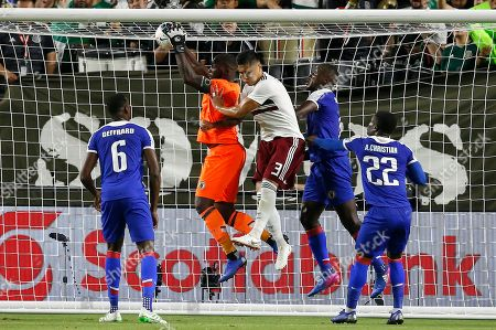 Haiti goalkeeper Jhony Placide, second from left, makes a save as he collides with Mexico defender Carlos Salcedo (3) as Haiti defender Jems Geffrard (6), Haiti defender Alex Christian (22) and Haiti defender Andrew Jean-Baptiste, second from right, look on during the first half of a CONCACAF Gold Cup soccer match, in Glendale, Ariz