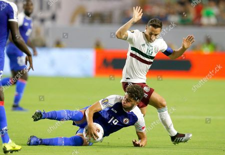 Haiti midfielder Steeven Saba and Mexico midfielder Andres Guardado (18) fight for the ball during the first half of a CONCACAF Gold Cup soccer match, in Glendale, Ariz
