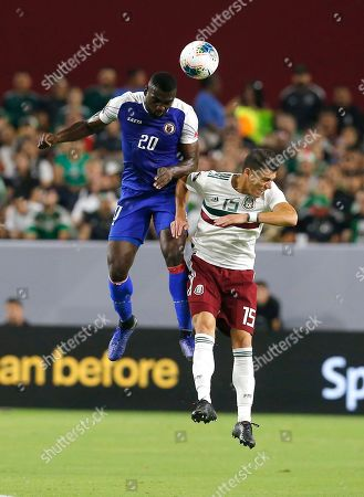 Mexico defender Hector Moreno (15) and Haiti forward Frantzdy Pierrot (20) during the first half of a CONCACAF Gold Cup soccer match, in Glendale, Ariz