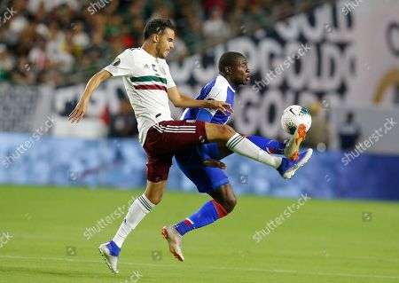 Mexico defender Diego Reyes (5) and Haiti midfielder Wilde-Donald Guerrier (10) during the first half of a CONCACAF Gold Cup soccer match, in Glendale, Ariz