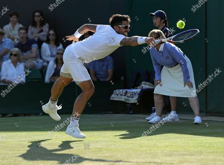 Serbia's Janko Tipsarevic returns to South Africa's Kevin Anderson in a Men's singles match during day three of the Wimbledon Tennis Championships in London
