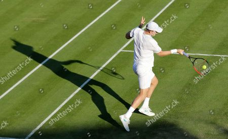 South Africa's Kevin Anderson casts a shadow as he returns to Serbia's Janko Tipsarevic in a Men's singles match during day three of the Wimbledon Tennis Championships in London