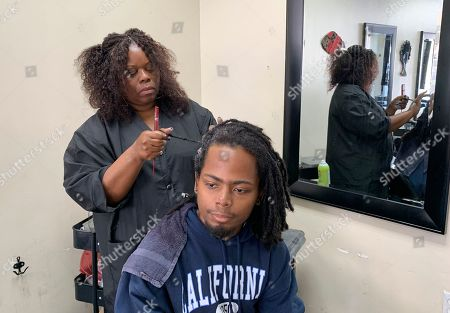 "Stock Image of Charlotte ""Peaches"" Smith, owner of the Dreadlocks Station salon, works on a customer's dreadlocks, in Oakland, Calif. California has become the first state to ban workplace and school discrimination against black people for wearing hairstyles such as braids, twists and locks"