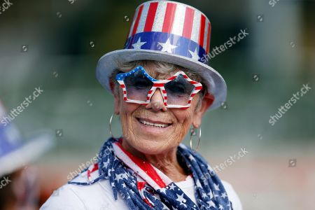 Linda Lee Stacy, of Ashbury, Mass., wears patriotic gear while waiting for the dress rehearsal for the Boston Pops Fireworks Spectacular in Boston