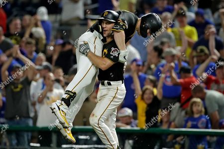 Pittsburgh Pirates' Corey Dickerson, top, is hoisted by Adam Frazier (26) after driving in the walk-off game winning run with a sacrifice fly off Chicago Cubs relief pitcher Craig Kimbrel during the ninth inning of a baseball game in Pittsburgh, . The Pirates won 6-5