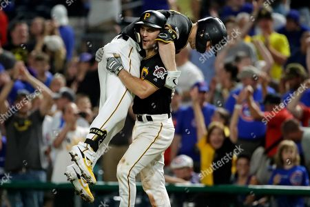Pittsburgh Pirates' Corey Dickerson, top center, celebrates with Adam Frazier (26) after driving in the walk-off game winning run with a sacrifice fly off Chicago Cubs relief pitcher Craig Kimbrel during the ninth inning of a baseball game in Pittsburgh, . The Pirates won 6-5