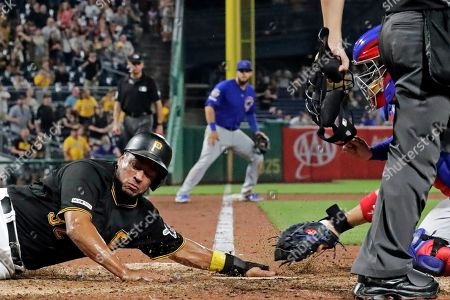 Pittsburgh Pirates' Elias Diaz, left, gets his hand under the tag attempt by Chicago Cubs catcher Victor Caratini, right, to score from third on a fielder's choice by Adam Frazier off Chicago Cubs relief pitcher Craig Kimbrel during the ninth inning of a baseball game in Pittsburgh, . The Pirates won 6-5