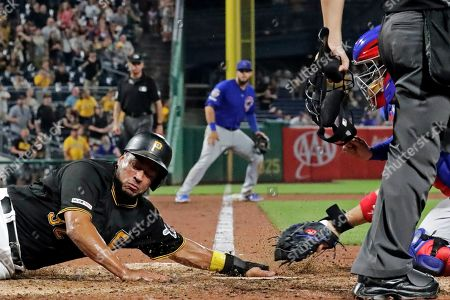 Elias Diaz, Victor Caratini. Pittsburgh Pirates' Elias Diaz, left, gets his hand under the tag attempt by Chicago Cubs catcher Victor Caratini, right, to score from third on a ball hit by Adam Frazier off Chicago Cubs relief pitcher Craig Kimbrel during the ninth inning of a baseball game in Pittsburgh, . The Pirates won 6-5