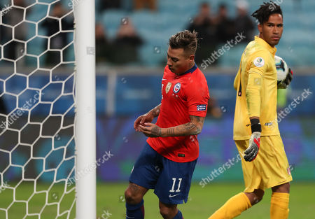 Peru's goalkeeper Pedro Gallese, right, holds the ball after blocking a penalty shot of Chile's Eduardo Vargas, left, during a Copa America semifinal soccer match at the Arena do Gremio in Porto Alegre, Brazil, . Peru defeated Chile 3-0 and qualified to the final