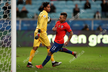 Peru's goalkeeper Pedro Gallese, left, holds the ball after blocking a penalty shot of Chile's Eduardo Vargas during a Copa America semifinal soccer match at the Arena do Gremio in Porto Alegre, Brazil, .Peru defeated Chile 3-0 and qualified to the final