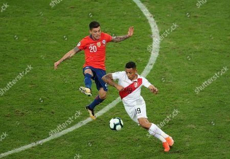 Stock Photo of Chile's Charles Aranguiz, left, and Peru's Victor Yotun battle for the ball during a Copa America semifinal soccer match at Arena do Gremio in Porto Alegre, Brazil