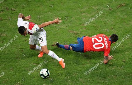 Peru's Victor Yotun, left, fights for the ball with Chile's Charles Aranguiz during a Copa America semifinal soccer match at Arena do Gremio in Porto Alegre, Brazil