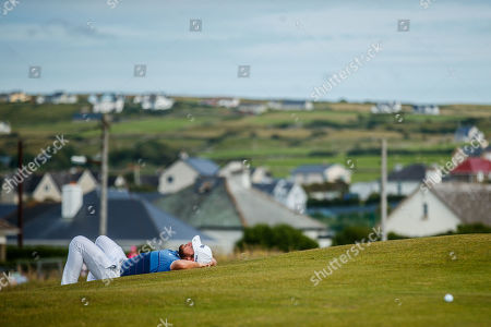 Tyrell Hatton of England takes a rest while the previous group finish putting on the 18th hole