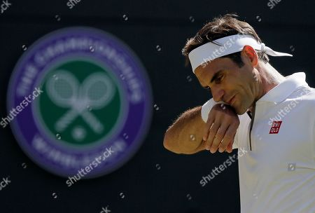 Switzerland's Roger Federer wipes his face as he plays Britain's Jay Clarke in a Men's singles match during day four of the Wimbledon Tennis Championships in London