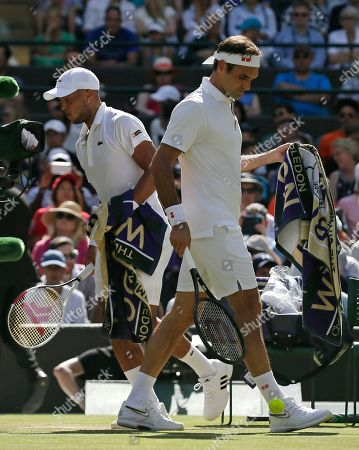 Switzerland's Roger Federer, right, and Britain's Jay Clarke change ends in a Men's singles match during day four of the Wimbledon Tennis Championships in London