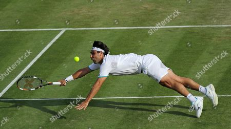 Marcos Baghdatis of Cyprus dives to return to Italy's Matteo Berrettini in a Men's singles match during day four of the Wimbledon Tennis Championships in London
