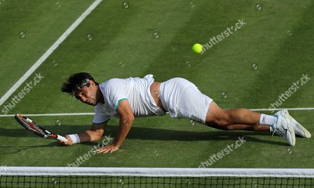 Marcos Baghdatis of Cyprus dives but fails to return to Italy's Matteo Berrettini in a Men's singles match during day four of the Wimbledon Tennis Championships in London