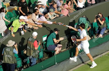 Marcos Baghdatis of Cyprus hands out racquets to spectators after after losing to Italy's Matteo Berrettini in a Men's singles match during day four of the Wimbledon Tennis Championships in London, . Baghdatis was set to retire after this championship