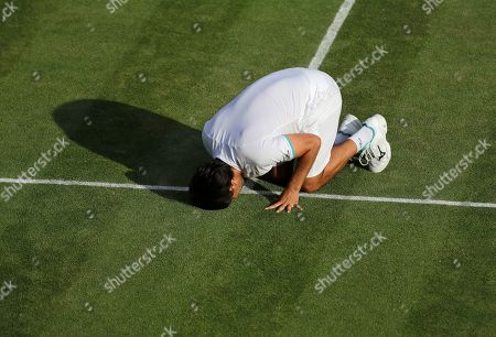 Marcos Baghdatis of Cyprus kisses the court after after losing to Italy's Matteo Berrettini in a Men's singles match during day four of the Wimbledon Tennis Championships in London, . Baghdatis was set to retire after this championship