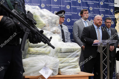 Attache of the Warsaw Office of United States Department of the Drug Enforcement Administration (DEA) Jason Schumacher (2-R) and Deputy Chief Regional Officer for the U.S. Department of the Drug Enforcement Administration (DEA) Kevin Daniels (R)  speaks while standing next to bags of cocaine, which were seized during a special police operation, at a press conference of the National Police and the Anti-Narcotic Police Department and the U.S. Department of the Drug Enforcement Administration (DEA) in the Ministry of Internal Affairs in Kiev.