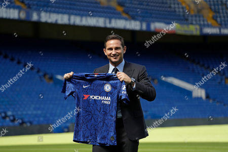 The new Chelsea manager their former player Frank Lampard poses for photographers with a club shirt by the pitch at Stamford Bridge stadium in London, . Lampard has returned to Chelsea as the club's 12th manager in 16 years under Roman Abramovich's ownership. The former Chelsea midfielder has left second-tier club Derby, where he came close to securing promotion to the Premier League in his first season in management. Lampard, who is Chelsea's record scorer with 211 goals and one of its all-time greats, replaces Maurizio Sarri
