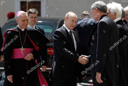 Russian President Vladimir Putin, followed by Archbishop Georg Gaenswein, left, is welcomed upon his arrival in the courtyard of San Damaso for his private audience with Pope Francis, at the Vatican, . Putin is scheduled to meet with Pope Francis at the Vatican and Italian leaders