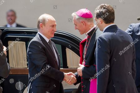 Russian President Vladimir Putin arrives at the Vatican for a private hearing and is welcomed by the Archbishop Georg Ganswein