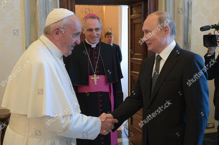 Pope Francis (L) and Russian President Vladimir Putin (R) shake hands as Archbishop Georg Ganswein (2-L) looks on during their meeting at the Vatican, 04 July 2019. Putin arrived for a one-day visit to Vatican and Rome to meet with the Pope and Italian leaders.