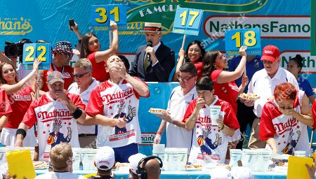 Competitive eaters George Chiger (L), Joey Chestnut (2-L) and Matt Stonie (2-R) and Max Suzuki (R) compete in the Nathan's Famous Fourth of July International Hog Dog Eating contest in Coney island in Brooklyn, New York, USA, 04 July 2019. Chestnut won the event for the twelfth time, eating 71 hot dogs.