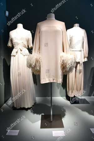 A pleated muslin dress with separate embroidered bodice (L), a Muslin cape dress with ostrich feathers (C) and a high collar blouse, matching belt, and harem pants (R) from the wardrobe of Italian actress Claudia Cardinale on display at Sotheby's auction house in Paris, France, 04 July 2019. Some 130 couture and ready-to-wear creations will go on sale in a public online auction, titled 'Claudia Cardinale: Dressing a Star', at Sotheby's on 09 July 2019.
